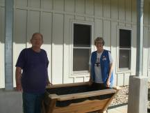 Two Red Cross volunteers assist with the new planter installation at Cottage D.