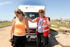 Moore, OK, May 23, 2013--Red Cross volunteer Peg Hume, sprays Aren Easom with suncreen. Red Cross is going through the neighborhoods impacted by the recent tornado on May 20, 2013. Residents impacted by the tornado are encouraged to register with FEMA. Jocelyn Augustino/FEMA